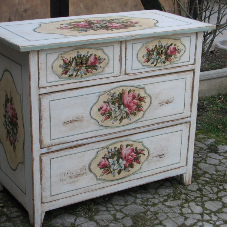 Malovaná bílá komoda s květinami v romantickém stylu.
